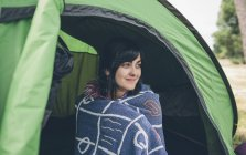 Smiling young woman sitting in a tent — Stock Photo