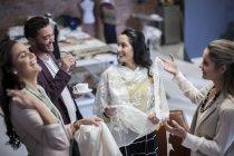 Felizes costureiras com cliente no showroom de moda — Fotografia de Stock