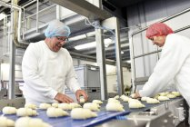 Workers working at production line in a baking factory with croissants — Stock Photo