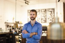 Confident young man standing in cafe with arms crossed — Stock Photo