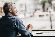 Mature man sitting in cafe — Stock Photo