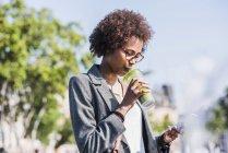 Женщина пьет напиток и пользуется смартфоном — стоковое фото