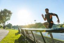 Athlète masculin en sautant par-dessus le banc à riverside — Photo de stock