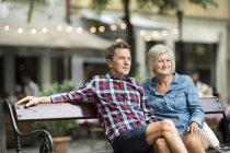Senior couple sitting on bench watching something — Stock Photo
