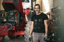 Portrait de sourire mécanique permanent le tracteur dans l'entrepôt — Photo de stock