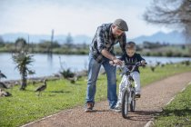 Father supporting son on bike at park — Stock Photo