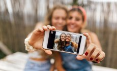 Selfie of two smiling teenage girls on display of smartphone — Stock Photo