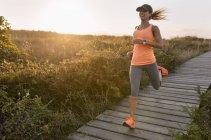 Jovem atleta mulher correndo ao longo de um caminho costeiro ao pôr do sol — Fotografia de Stock