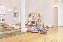 Улыбающаяся женщина сидит в студии йоги — стоковое фото