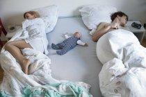 Parents de dormir avec bébé dans son lit — Photo de stock