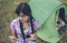 Jovem na frente de uma tenda com xícara de café ouvindo música com fones de ouvido — Fotografia de Stock