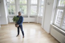 Man holding plant in empty apartment — Stock Photo