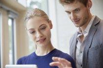 Homem e mulher compartilhando tablet — Fotografia de Stock