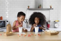 African american brother feeding his sister with a spoon — Stock Photo