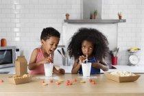Afrikanische amerikanische Bruder seine Schwester mit einem Löffel füttern — Stockfoto
