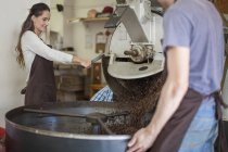 Colleagues at coffee roasting machine — Stock Photo