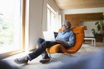 Зрелый мужчина, использующий ноутбук в кресле — стоковое фото