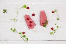 Wild strawberry ice lollies on wood — Stock Photo
