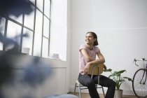 Young woman sitting on chair, looking out of window — Stock Photo