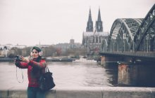 Germany, Cologne, woman with ear muff taking selfie with polaroid camera — Stock Photo