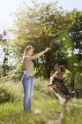 Young woman taming her mongrel on a meadow — Stock Photo