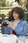 Smiling young woman with old camera sitting in a sidewalk cafe — Stock Photo