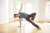 Человек в солнечной студии йоги, держащий позу Васистасаны — стоковое фото