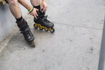 Cropped image of man putting on rollerblades outdoors — Stock Photo