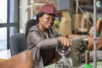 Portrait of smiling woman working at sewing machine in workshop — Stock Photo