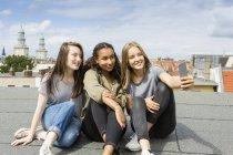 Німеччина, Берлін, трьох дівчат-підлітків сидячи на покрівлі верхній беручи selfie зі смартфона — стокове фото