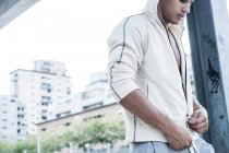 Fit young man wearing hooded jacket in city — Stock Photo