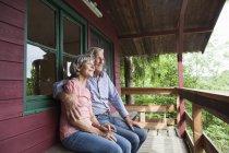 Feliz pareja senior relajante en el porche de la cabaña - foto de stock