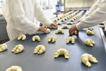 Travailleurs à la ligne de production dans une usine de boulangerie avec croissants — Photo de stock