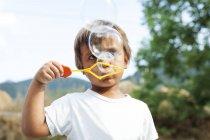 Kleiner Junge pustet Seifenblasen — Stockfoto