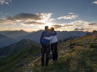 Couple kissing at sunset in the mountains — Stock Photo