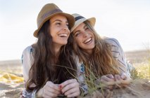 Portrait of two best friends with summer hats lying on the beach — Stock Photo