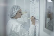 Lab technician in sterile protective clothing writing notes on whiteboard — Stock Photo