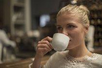 Giovane donna che beve la tazza di caffè in un bar — Foto stock