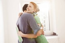 Happy young couple hugging at the window — Stock Photo