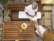 Senior man sitting on terrace — Stock Photo