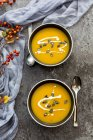 Creamed pumpkin soup in black bowls on grey tabletop — Stock Photo