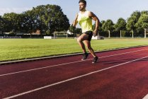 Athlete exercising on tartan track — Stock Photo