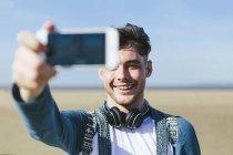 Селф принимая человек с смартфон — стоковое фото