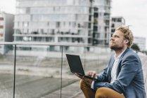 Businessman sitting on bridge using laptop — Stock Photo