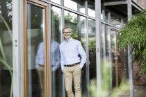 Lächelnder Mann lehnt an Fassade seines Hauses — Stockfoto