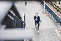 Young businessman riding bike while talking on the phone — Stock Photo