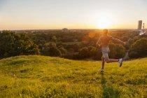 Сорочки людина, що біжить на галявині в парку на заході сонця — стокове фото