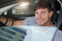 Portrait of smiling young man sitting in car — Stock Photo