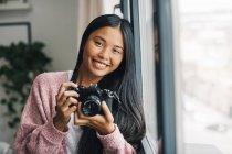 Женщина с камерой смотрит в камеру — стоковое фото