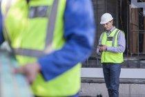 Männer mit Handy auf Baustelle — Stockfoto